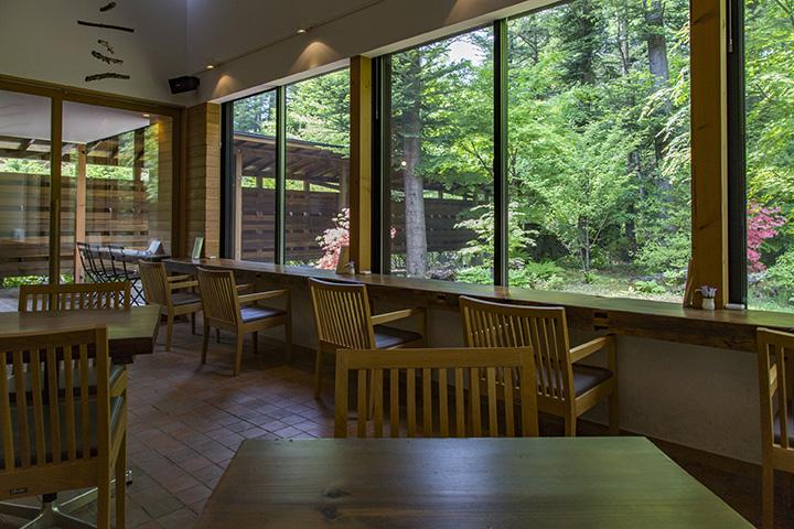 一枚板のカウンター席ほか、テーブル席もある。窓の外には豊かな自然