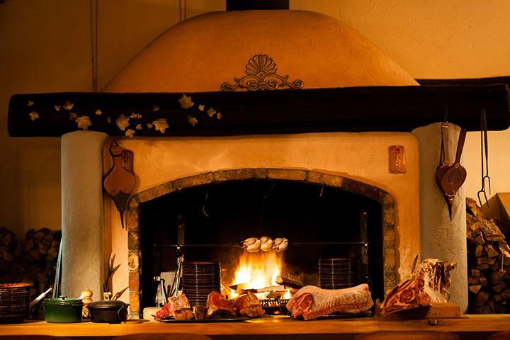 薪の量や距離を調節しながら肉に火を通すのは職人技