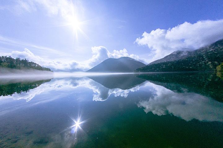 鏡のように景色を映し出す然別湖。正面にはくちびる山