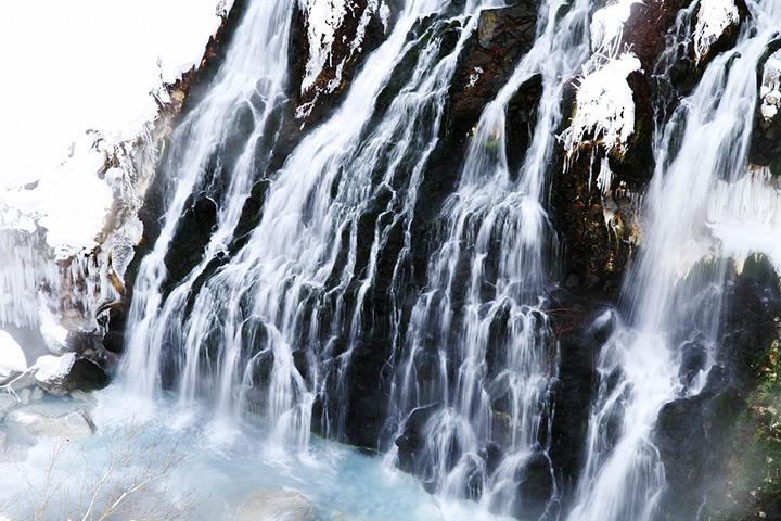 岩肌の黒と白い滝、青い渓流が美しい