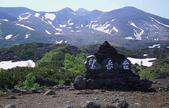 登山道の入り口にある望岳台の積み石と十勝岳