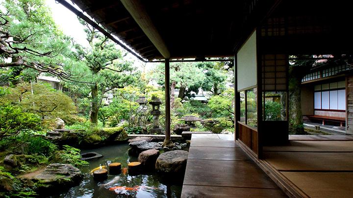 樹木と灯篭、庭石、曲水が美しく配された庭園と濡れ縁
