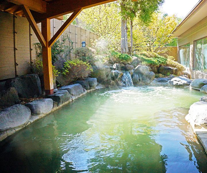 翠(みどり)色に変化した露天風呂。泉温は39℃と低めで、長湯向き