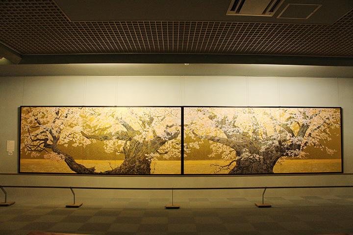 金屏風に描かれた作品「桜花浄苑雙図(おうかじょうえんそうず)」