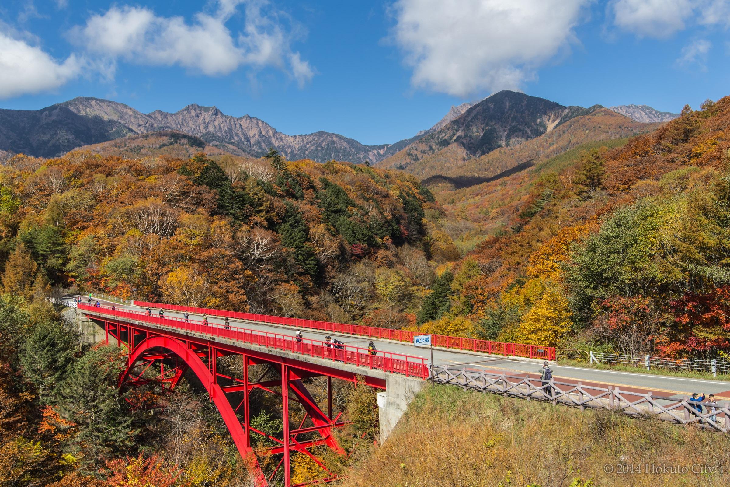 渓谷の紅葉に映える赤いアーチ橋