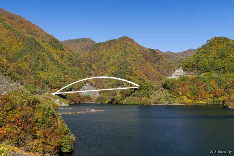 湖面に映り込む紅葉と白い橋の絶景コラボ