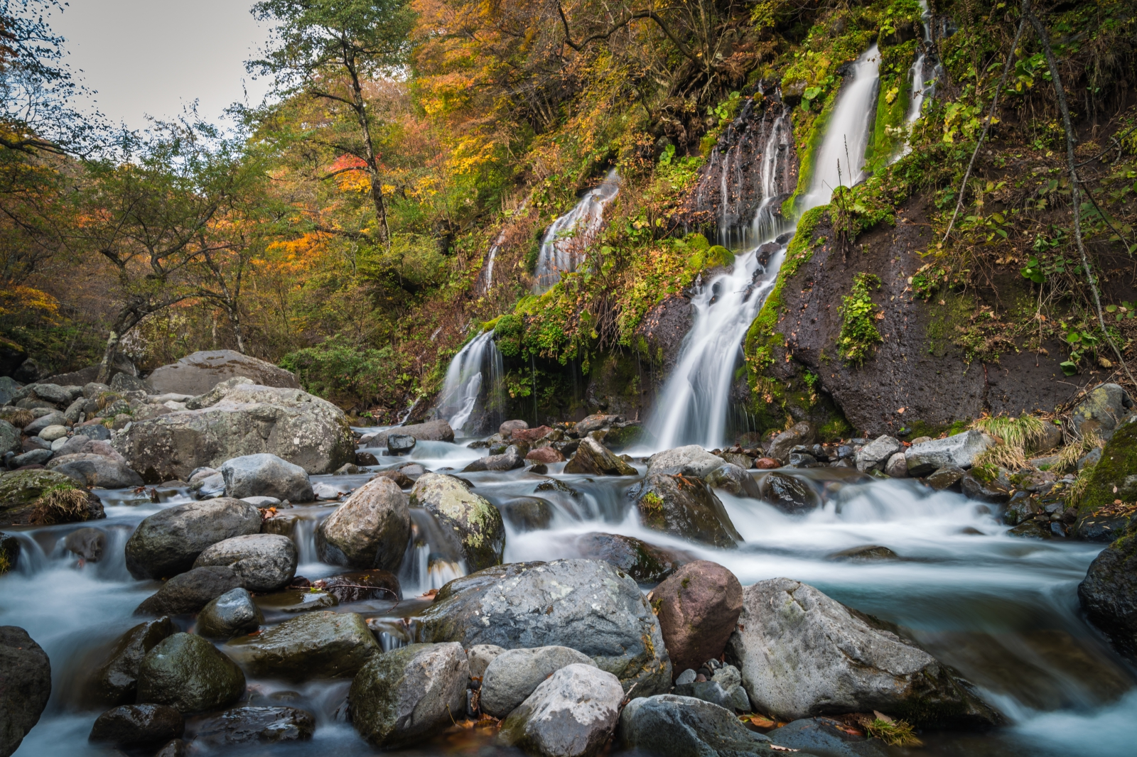 紅葉の中を流れる絹糸の滝が優美