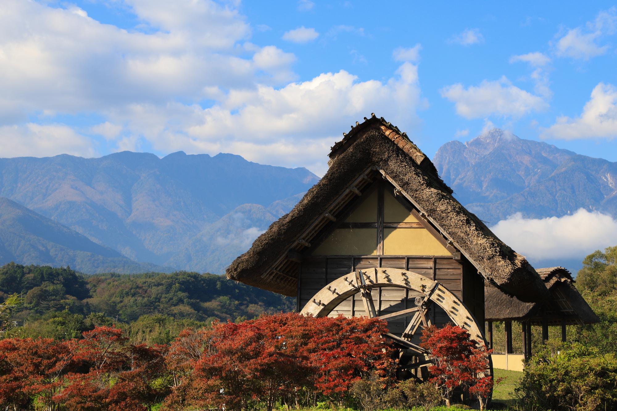 八ヶ岳の紅葉と茅葺きの水車が織りなす癒しの田園風景