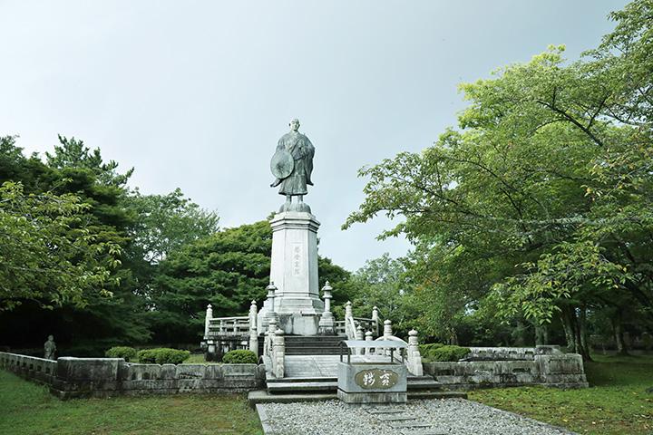 高さ約5mの蓮如上人(れんにょしょうにん)の銅像。広場には御本堂跡なども残されている