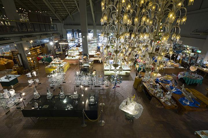 吹き抜けに掛かる1億円のシャンデリア。1階のフロアにはグラス類の他、アクセサリーも多数