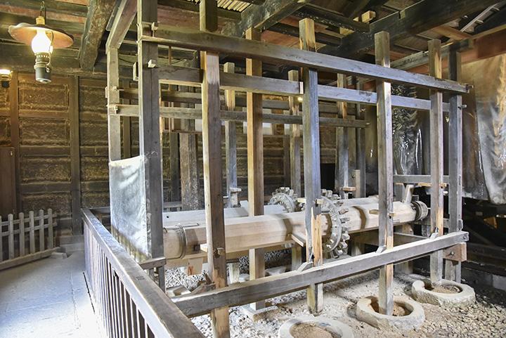 藩米精米所。水車で木製の歯車が回り、木の棒が米をつく仕組み