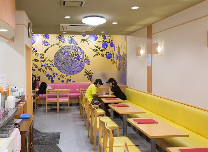 黄色を基調にした店内奥に果物が躍動する障壁画が映える