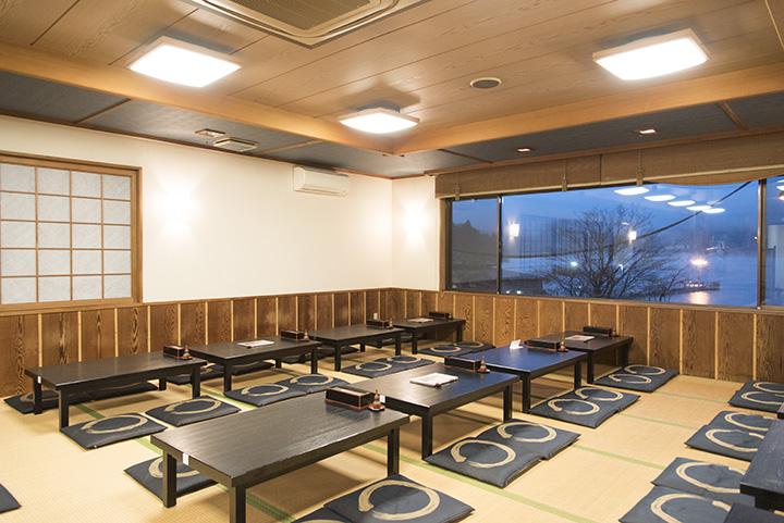1階はテーブル席。約80名座れる2階の大広間。窓の外には湖に浮かぶ遊覧船が