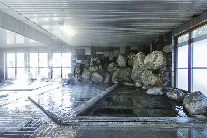 広々とした旧館の岩風呂。新館と合わせて多彩な湯船に浸かれるのがうれしい