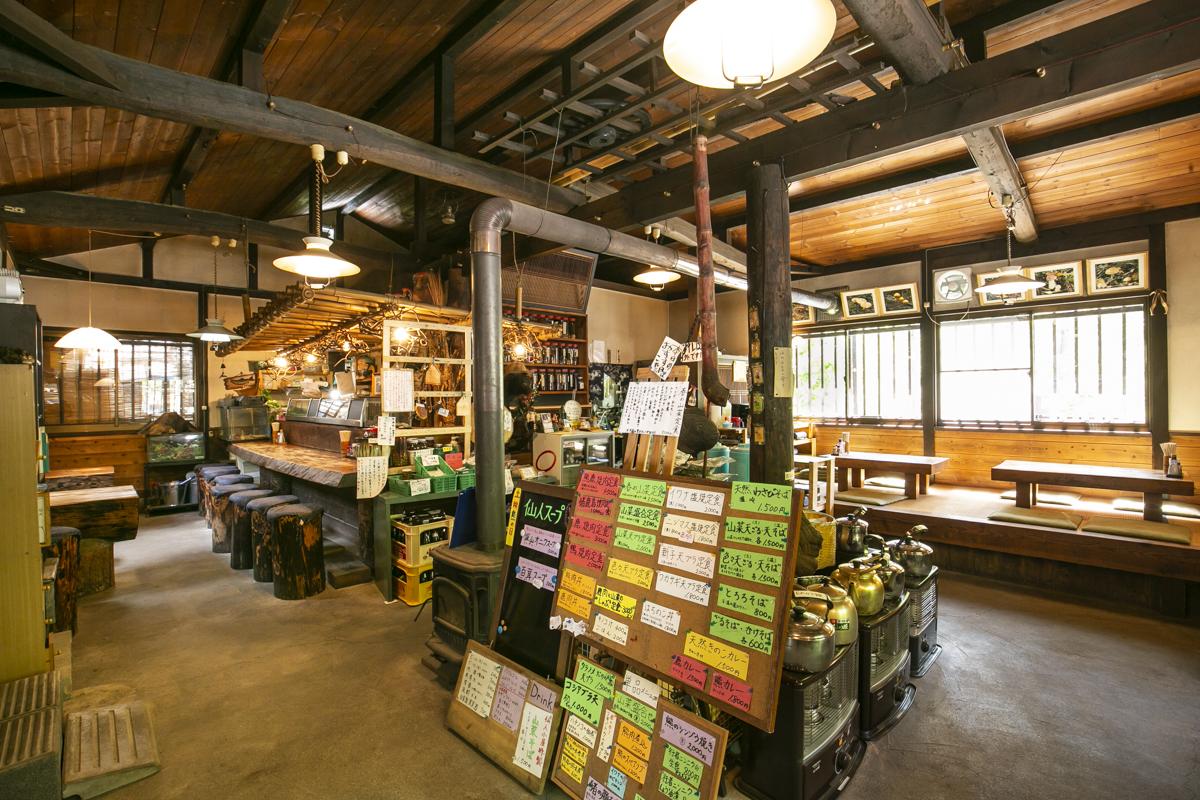 大きな囲炉裏(いろり)がある山小屋風の建物。店内ではキノコの塩漬けや手作りのお茶なども販売