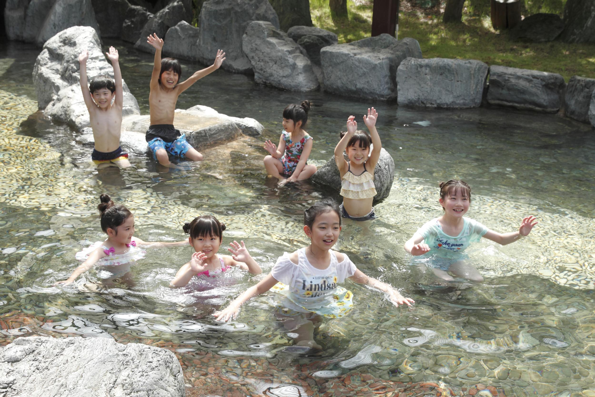 大露天風呂では水着か湯あみ着を着用。他に陶器風呂や男女別の木曾ひのき露天風呂、自然石露天風呂もある多彩な湯処