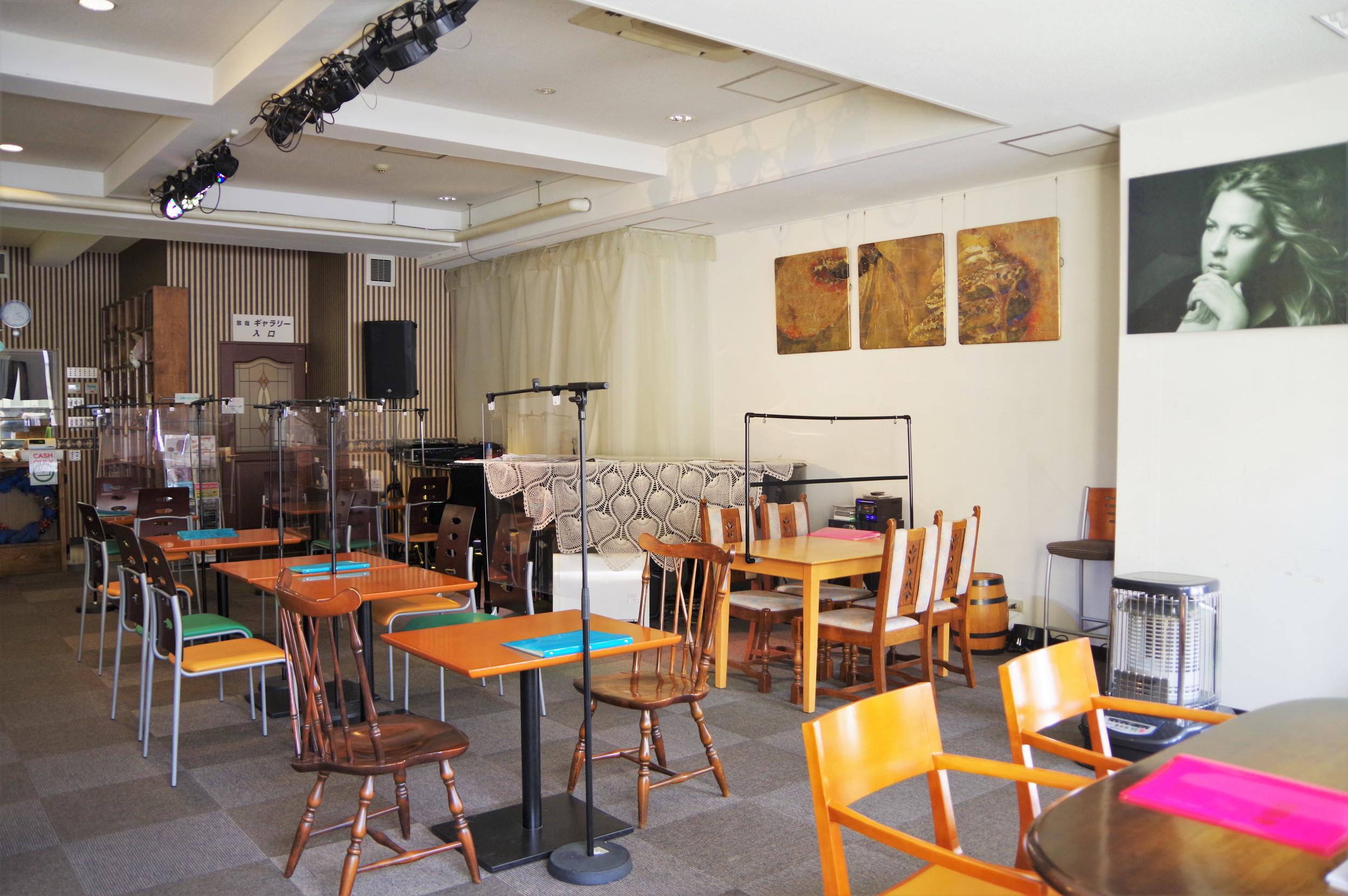 店内の一角にはグランドピアノや大型スピーカーなどがあり、天井にはスポットライトも吊るされています