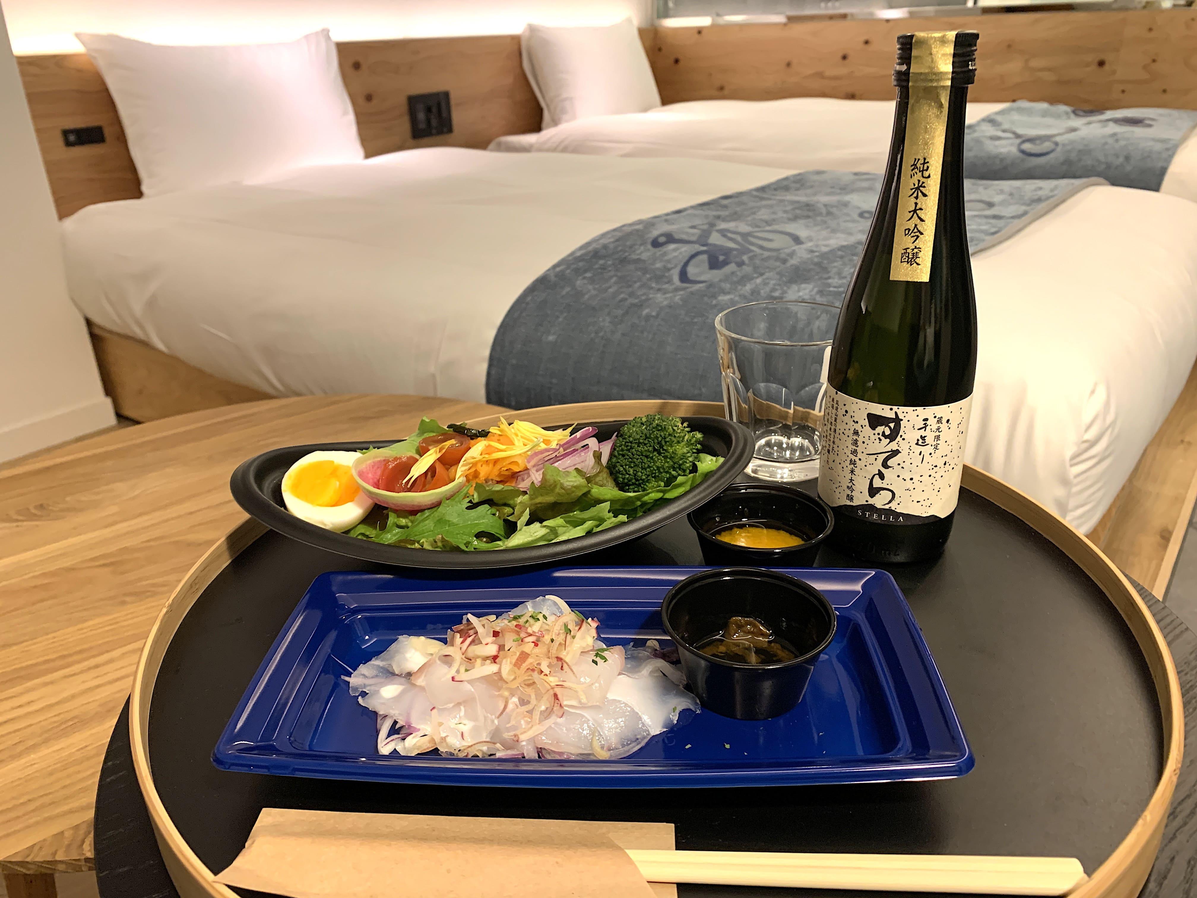 客室にてアトレで買った地酒と惣菜で乾杯。「TAMARIBA」ラウンジも食事場所に使える。
