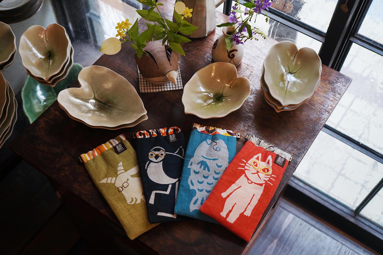 クワズイモの葉がモチーフの器1,800円〜、個性豊かなヤギやヤマネコなどが描かれた布製のメガネケース3,800円